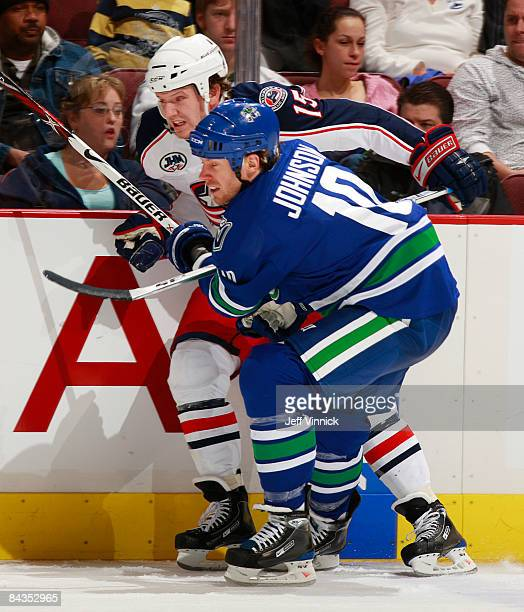 Ryan Johnson of the Vancouver Canucks and Jamie Langenbrunner of the New Jersey Devils battle along the boards during their game at General Motors...