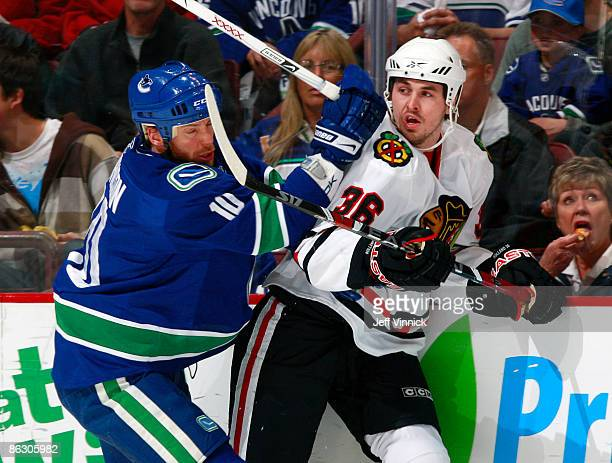 Ryan Johnson of the Vancouver Canucks hits Dave Bolland of the Chicago Blackhawks along the boards during Game One of the Western Conference...