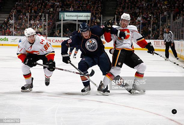 Ryan Jones of the Edmonton Oilers fights off Jon Rheault and TJ Brodie of the Calgary Flames in secondperiod action at Rexall Place October 1 2010 in...