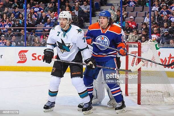 Ryan Jones of the Edmonton Oilers looks for an opportunity in front of the net as Brad Stuart of the San Jose Sharks defends during an NHL game at...