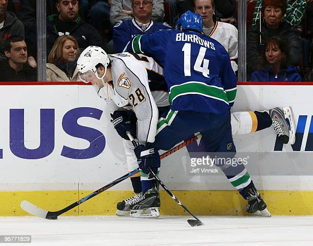 Ryan Jones of the Nashville Predators is checked by Alex Burrows of the Vancouver Canucks during their game at General Motors Place on January 11...