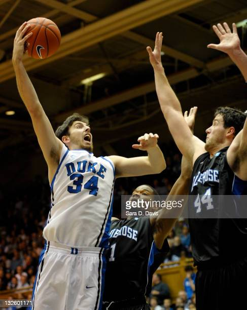 Ryan Kelly of the Duke Blue Devils drives toward the basket over Joshua Clyburn and Jay Reynolds of the Presbyterian Blue Hose during an NCAA game in...