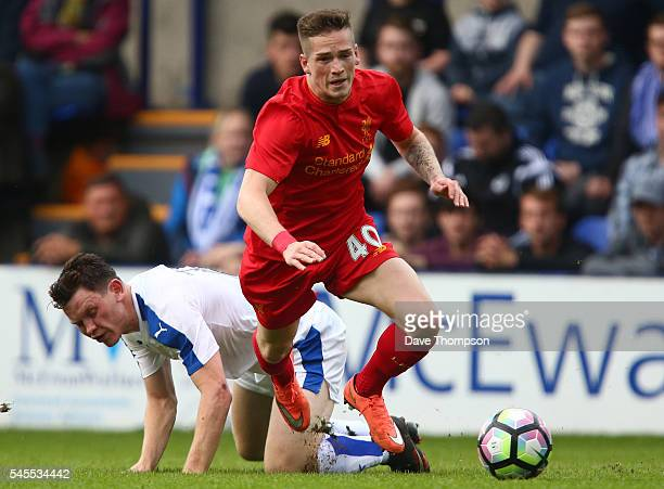 Ryan Kent of Liverpool gets past Connor Jennings of Tranmere Rovers during the PreSeason Friendly match between Tranmere Rovers and Liverpool at...