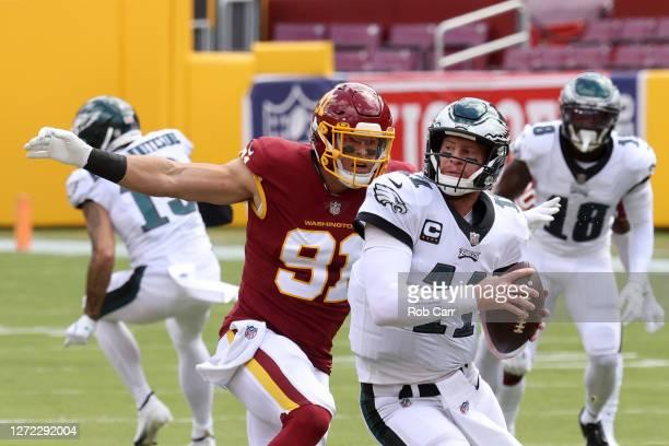 Ryan Kerrigan of the Washington Football Team sacks quarterback Carson Wentz of the Philadelphia Eagles in the first half at FedExField on September...