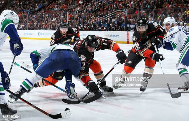 Ryan Kesler and Patrick Eaves of the Anaheim Ducks battle in a faceoff against Brendan Gaunce of the Vancouver Canucks during the game on March 4...