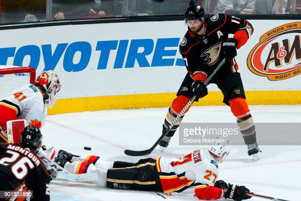 Ryan Kesler of the Anaheim Ducks passes the puck to Brandon Montour with pressure from Dougie Hamilton and Mike Smith of the Calgary Flames during...