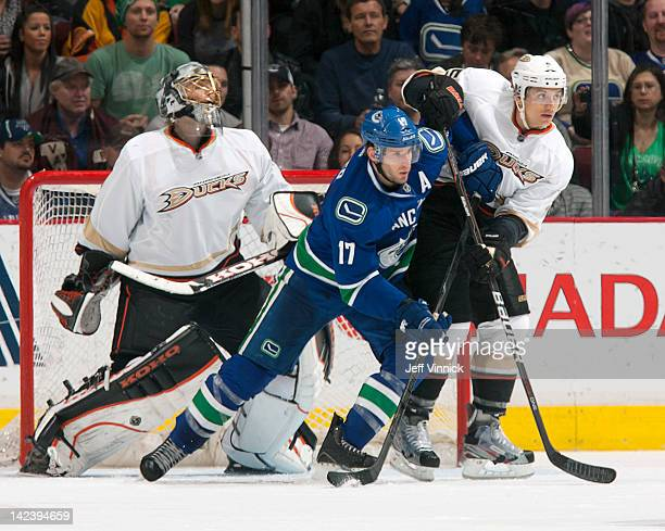 Ryan Kesler of the Vancouver Canucks and Luca Sbisa of the Anaheim Ducks battle for position in front of Jonas Hiller of the Ducks during their NHL...