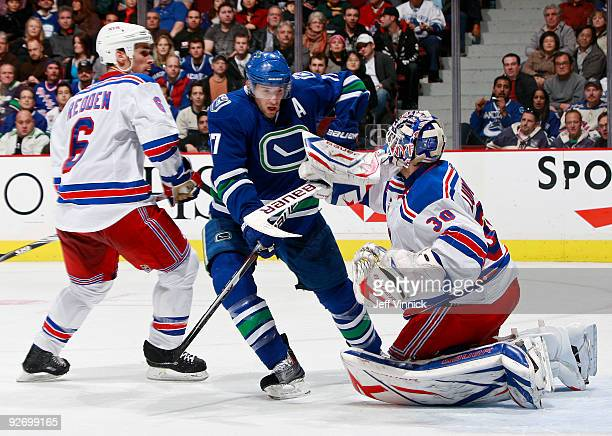Ryan Kesler of the Vancouver Canucks battles for position in front of the net against Wade Redden of the New York Rangers and teammate Henrik...