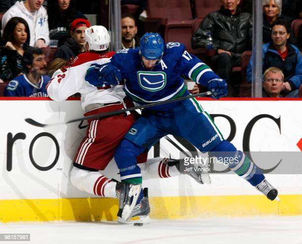 Ryan Kesler of the Vancouver Canucks checks Derek Morris of the Phoenix Coyotes into the boards during their game at General Motors Place on March 30...