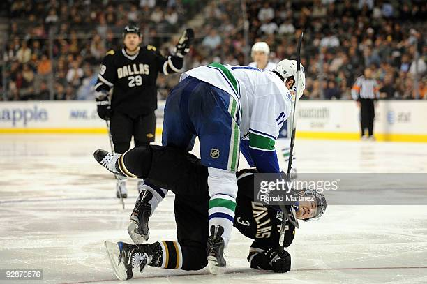 Ryan Kesler of the Vancouver Canucks falls on top of Stephane Robidas of the Dallas Stars during NHL action at American Airlines Center on November...
