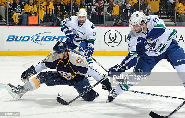Ryan Kesler of the Vancouver Canucks flips the puck under Jonathon Blum of the Nashville Predators in Game Three of the Western Conference Semifinals...