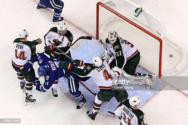 Ryan Kesler of the Vancouver Canucks gets pushed by Clayton Stoner of the Minnesota Wild after scoring the goal in the second period at Rogers Arena...