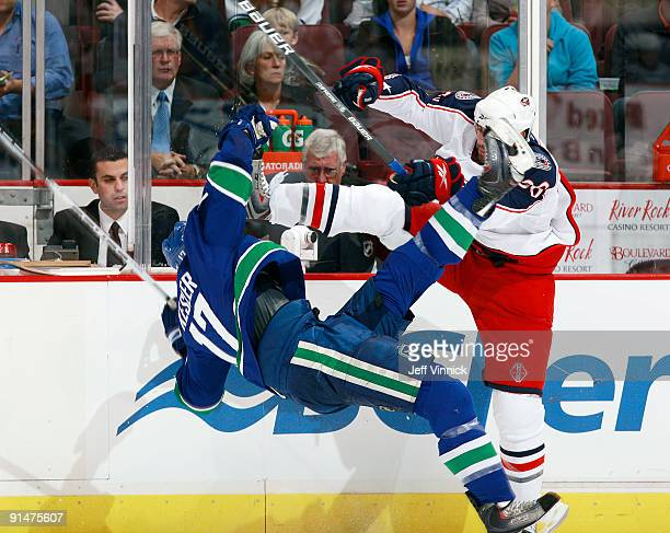 Ryan Kesler of the Vancouver Canucks is checked to the ice by Mathieu Roy of the Columbus Blue Jackets during their game at General Motors Place on...