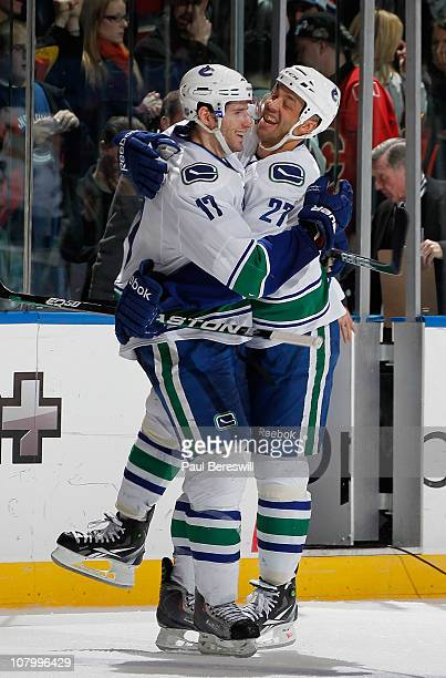 Ryan Kesler of the Vancouver Canucks is hugged by teammate Manny Malhotra as they celebrate the winning goal by Kesler in the shootout of an NHL...