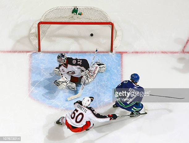 Ryan Kesler of the Vancouver Canucks scores on Mathieu Garon of the Columbus Blue Jackets while Antoine Vermette of the Columbus Blue Jackets looks...