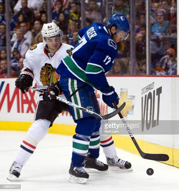 Ryan Kesler of the Vancouver Canucks tries to fight off the check of Michael Frolik of the Chicago Blackhawks during the third period in NHL action...