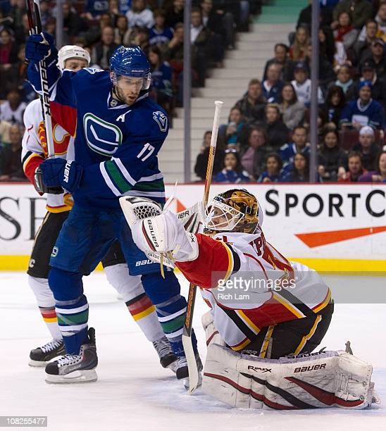 Ryan Kesler of the Vancouver Canucks watches goalie Miikka Kiprusoff of the Calgary Flames make a glove save during the second period in NHL action...