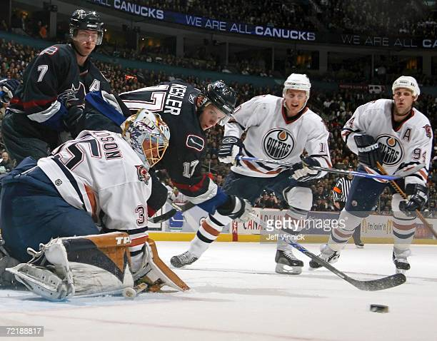 Ryan Kesler of the Vancouver Canucks watches his rebound after Dwayne Roloson of the Edmonton Oilers makes a save as Brendan Morrison of the...