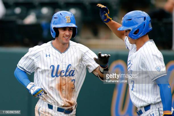 Ryan Kreidler of UCLA high-fives teammate Michael Toglia following Kreidler's second home run during a baseball game against University of Washington...