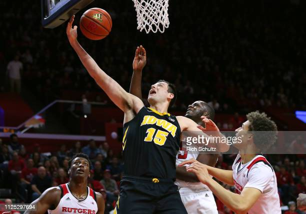 Ryan Kriener of the Iowa Hawkeyes attempts a layup as Eugene Omoruyi and Caleb McConnell of the Rutgers Scarlet Knights defend during the first half...