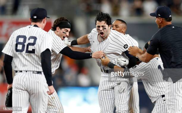 Ryan LaMarre of the New York Yankees celebrates his tenth inning game winning base hit against the Philadelphia Phillies with his teammates at Yankee...