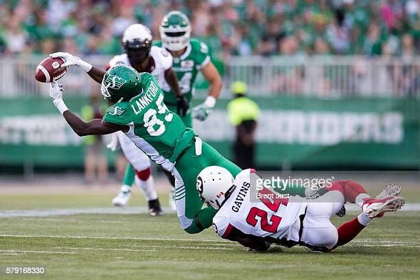 Ryan Lankford of the Saskatchewan Roughriders fails to make this catch as he is dragged down by Jerrell Gavins of the Ottawa Redblacks in the game...