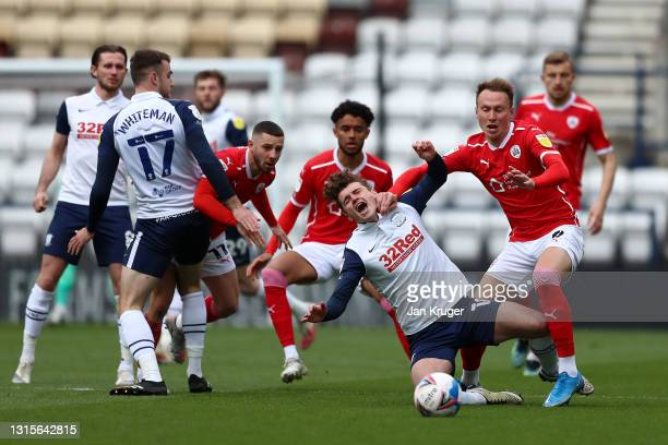 Ryan Ledson of Preston North End is challenged by Cauley Woodrow of Barnsley during the Sky Bet Championship match between Preston North End and...