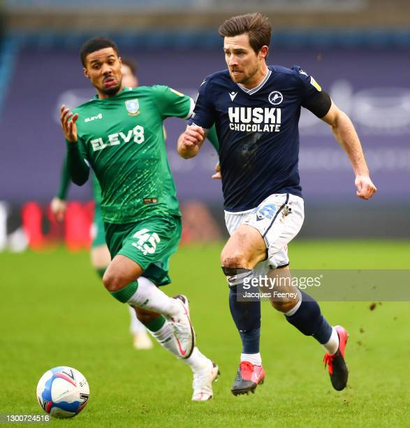Ryan Leonard of Millwall FC is put under pressure by Elias Kachunga of Sheffield Wednesday during the Sky Bet Championship match between Millwall and...