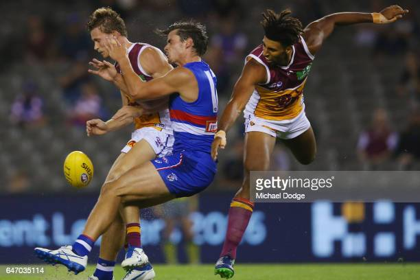 Ryan Lester of the Lions crunches Tom Boyd of the Bulldogs in a contest for the ball during the 2017 JLT Community Series AFL match etween the...