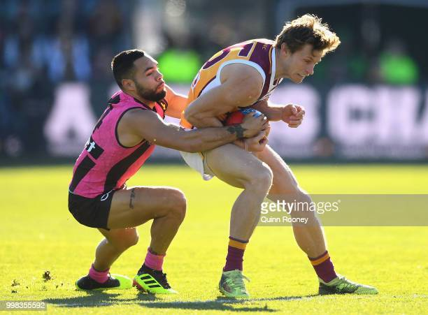 Ryan Lester of the Lions is tackled by Jarman Impey of the Hawks during the round 17 AFL match between the Hawthorn Hawks and the Brisbane Lions at...