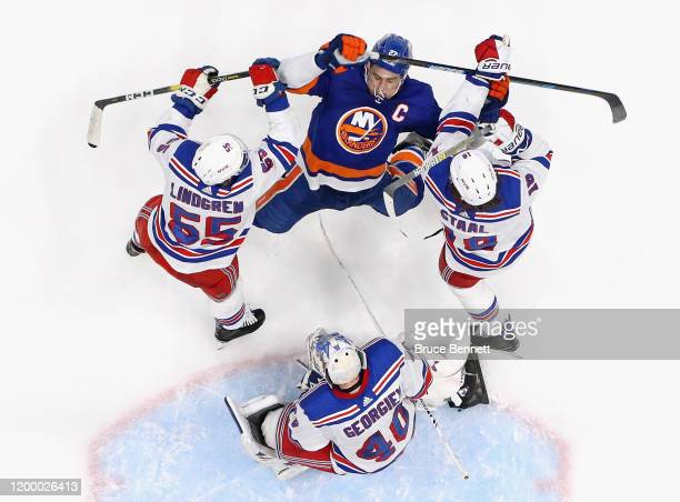 Ryan Lindgren and Marc Staal of the New York Rangers defend against Anders Lee of the New York Islanders during the third period at NYCB Live's...