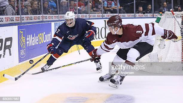 Ryan Lindgren of Team USA knocks the puck away from Rihards Puide of Team Latvia during a 2017 IIHF World Junior Hockey Championship game at the Air...