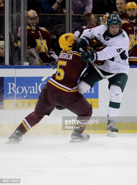 Ryan Lindgren of the Minnesota Golden Gophers collides with Patrick Khodorenko of the Michigan State Spartans in the third period during their game...