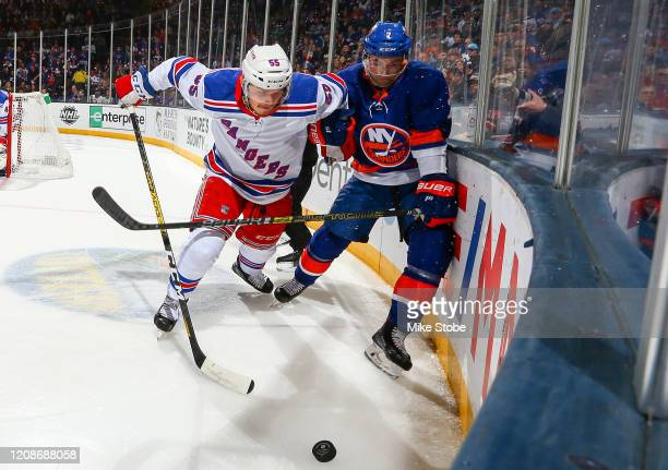 Ryan Lindgren of the New York Rangers and Nick Leddy of the New York Islanders battle for the puck during the first period at NYCB Live's Nassau...