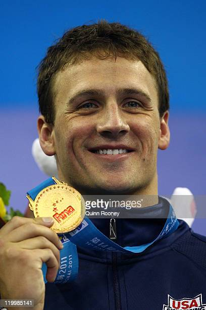 Ryan Lochte of the United States poses with his gold medal after winning in a new world record time the Men's 200m Individual Medley Final during Day...