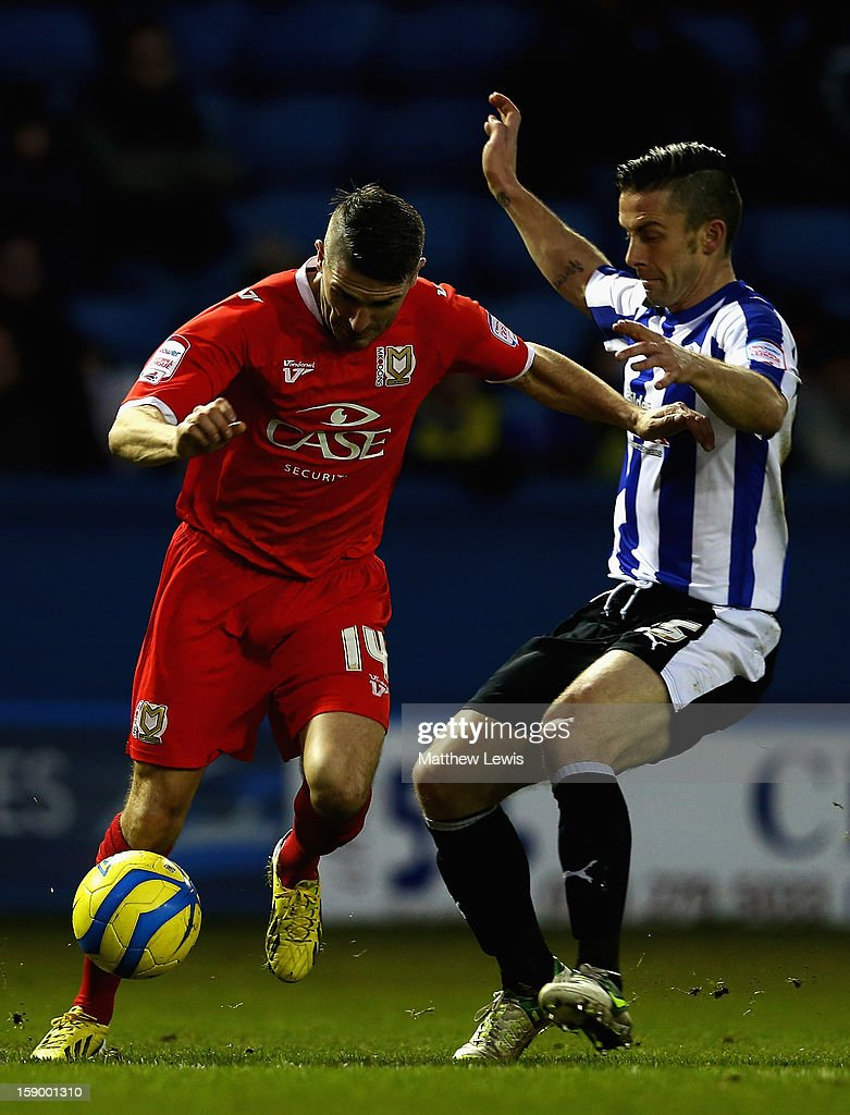 Ryan Lowe of Milton Keynes is tackled by David Prutton of Sheffield during the FA Cup with Budweiser Third Round match between Sheffield Wednesday and Milton Keynes Dons at Hillsborough Stadium on January 5, 2013 in Sheffield, England.