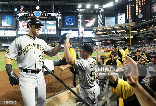 Ryan Ludwick of the Pittsburgh Pirates highfives pitching coach Gregg Ritchie after hitting a solo home run against the Arizona Diamondbacks during...