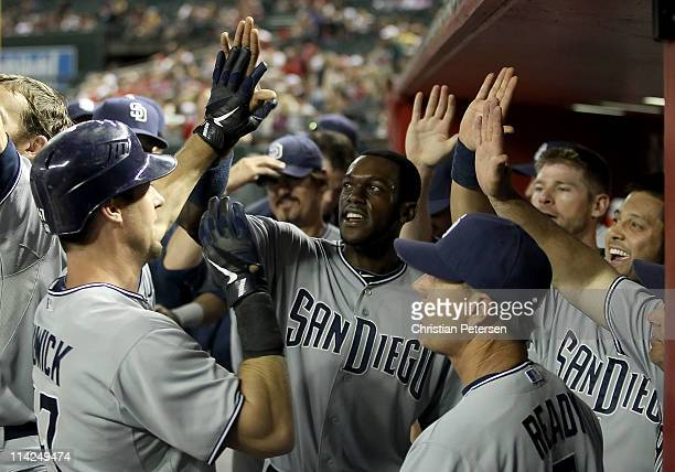 Ryan Ludwick of the San Diego Padres highfives teammate Cameron Maybin in the dugout after hitting a tworun home run against the Arizona Diamondbacks...