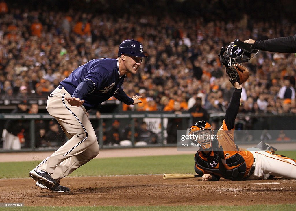Ryan Ludwick #47 of the San Diego Padres reacts after safely sliding past Buster Posey #28 of the San Francisco Giants to give the Padres a 3-2 lead on a fielders choice hit by Chase Headley #7 in the sixth inning at AT&T Park on August 13, 2010 in San Francisco, California.
