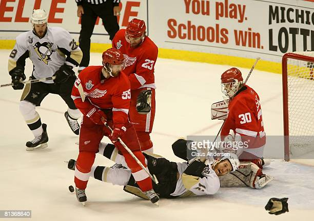 Ryan Malone of the Pittsburgh Penguins is struck by a puck in the face in front of goaltender Chris Osgood Brad Stuart and Niklas Kronwall of the...