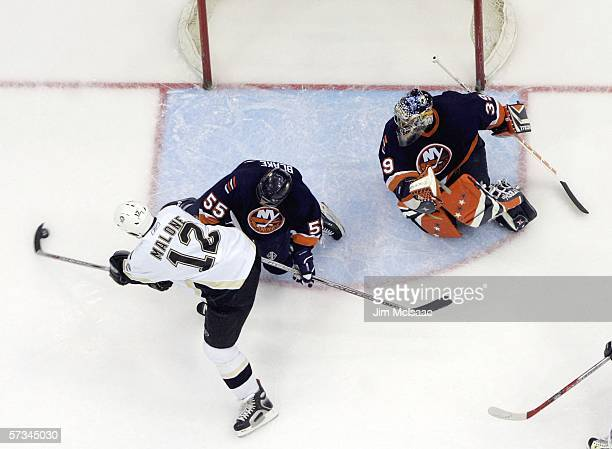 Ryan Malone of the Pittsburgh Penguins misses an open net against Jason Blake and goalie Rick DiPietro of the New York Islanders during their game on...