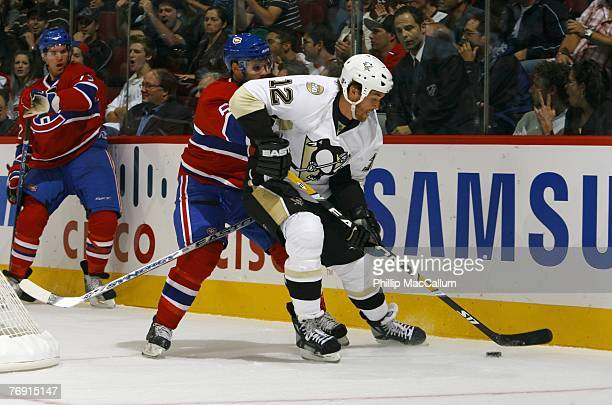 Ryan Malone of the Pittsburgh Penguins plays the puck as he is pressured by Tom Kostopoulos of the Montreal Canadiens during a pre-season game on...