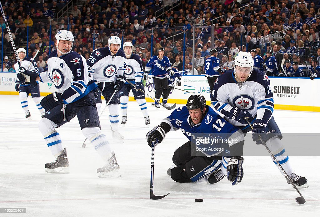 Ryan Malone #12 of the Tampa Bay Lightning and Grant Clitsome #24 of the Winnipeg Jets fight for possession of the puck during the third period of the game at the Tampa Bay Times Forum on February 1, 2013 in Tampa, Florida.