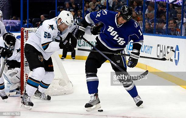 Ryan Malone of the Tampa Bay Lightning and Matt Irwin of the San Jose Sharks battle for a puck at the Tampa Bay Times Forum on January 18 2014 in...