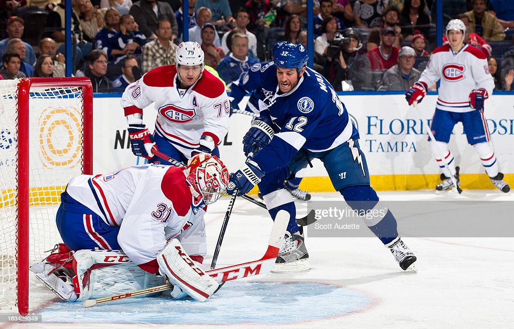Ryan Malone #12 of the Tampa Bay Lightning fights for a rebound while goalie Carey Price #31 of the Montreal Canadiens blocks during the first period of the game at the Tampa Bay Times Forum on March 9, 2013 in Tampa, Florida.