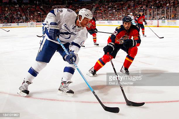 Ryan Malone of the Tampa Bay Lightning passes the puck against Jason Garrison of the Florida Panthers at the BankAtlantic Center on November 25 2011...