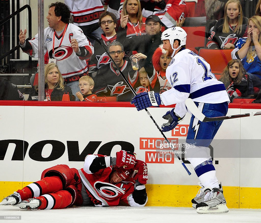 Ryan Malone #12 of the Tampa Bay Lightning stands over Eric Staal #12 of the Carolina Hurricanes after driving him into the boards during play at PNC Arena on January 22, 2013 in Raleigh, North Carolina.