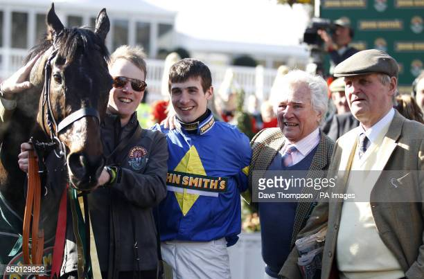 Ryan Mania returns to the winning enclosure with Auroras Encore, part-owner Jim Beaumont and Harvey Smith after winning the John Smiths' Grand...