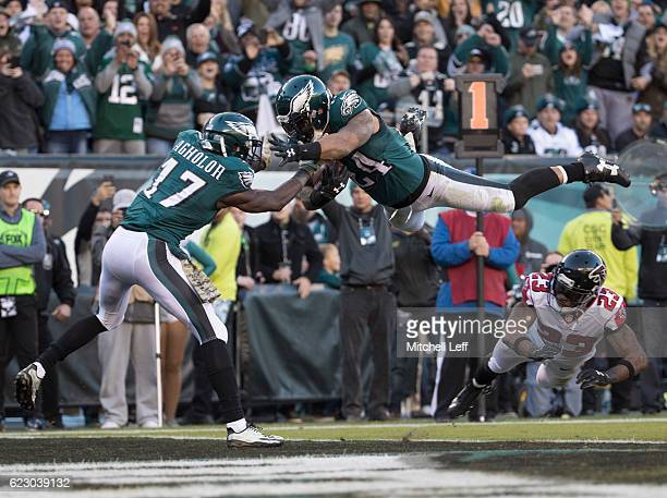 Ryan Mathews of the Philadelphia Eagles jumps over Robert Alford of the Atlanta Falcons to score a touchdown as Nelson Agholor tries to catch him in...