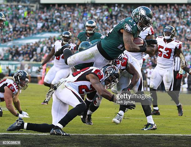 Ryan Mathews of the Philadelphia Eagles leaps over Robert Alford of the Atlanta Falcons to score a touchdown in the fourth quarter during a game at...